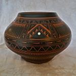 Red clay pottery with feathers and fine geometrics designs